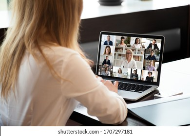 View over businesswoman shoulder sit at workplace desk looks at pc screen during group videocall with different age and ethnicity colleagues using application and webcam, distant communication concept