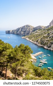 View over the calanque de Morgiou on the mediterranean shore near Marseille, France, with sailboats mooring in the turquoise waters and the cap Morgiou in the distance on a sunny spring day.