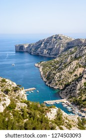 View over the calanque de Morgiou on the mediterranean shore near Marseille in the south of France, with its small port and the cap Morgiou in the distance on a sunny spring day.