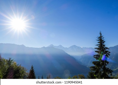 View over the city of Interlaken and the alps, mountains Eiger Moench and Jungfrau, lakes, the sun shinging brightly