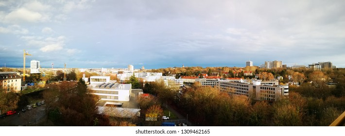 a view over city of Mainz, Rhineland-pfalz, Germany. Taken from high building towering over the city. Clouds and buildings appear in the photo.
