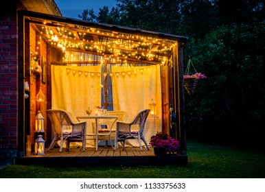 View over cozy outdoor terrace with table and chairs, very romantic lighting, white lanterns, candles burning, led string party lights and bulbs with star effect, in the evening.