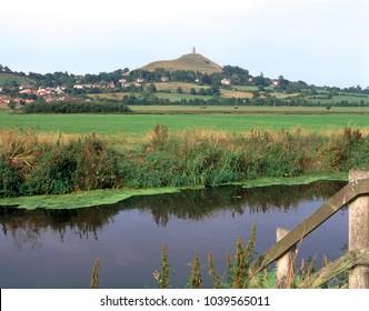 View over a drainage rhyne near Glastonbury towards historic Glastonbury Tor, Somerset, UK