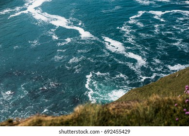 view from over the edge of a 600 foot cliff into the ocean