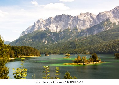 View over the Eibsee near the Zugspitze. The Eibsee have several small islands and is a famous visiting spot. The highest mountain and point in Gemany is the Zugspitze in the background near Grainau.