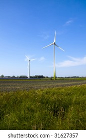 View over a farmers field with two wind turbines and solar energy cells
