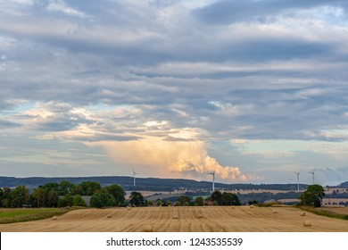 View over farmland and big cumulonimbus cloud in the background in Sweden