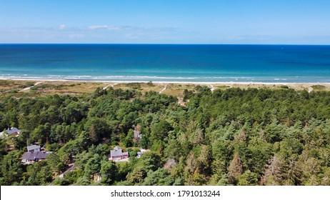 Blick von über Wald mit Blick auf Strand mit Meer (4k) (Lufttrommel-Foto)