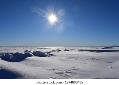 view over frozen lake on a sunny winter day with blue sky and snow on ice glittering in sunlight at Fort Peck Lake in Montana