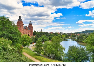 View over German city Aschaffenburg with Main river, palace called 'Schloss Johannisburg' and green park on sunny summer day