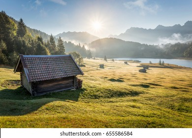 View over Geroldsee with wooden hut and Karwendel mountains at early morning in autumn, Bavaria, Germany