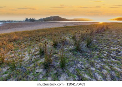 view over a grass and sand estuary sandbar with setting sun and distant yellow clouds