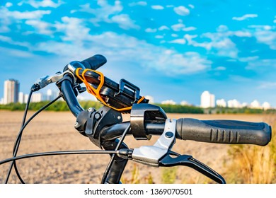 View over the handlebar of a bicycle. In the background you can see a field and the unfocussed satellite town of Gropiusstadt in Berlin-Neukölln.