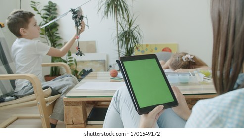 View over head on of caucasian woman working at home. Children play and take lessons on the background. Girl holding tablet computer with green screen chroma key.