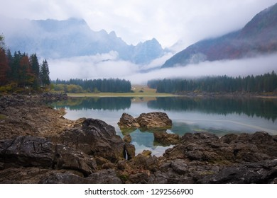 View over lake Laghi di Fusine on a foggy morning with some rocks at the beach and mountain range Mangart near Tarvisio in Italy