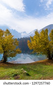 View over lake Laghi di Fusine to mountain range Mangart near Tarvisio in Italy on a sunny morning with some clouds and fog in autumn