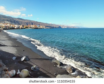"""View over the lava beach at high tide in the direction of """"Santa Cruz de Tenerife"""" In the foreground light and dark gray smooth washed  large stones.The Atlantic in dark blue-green, as well as the sky"""