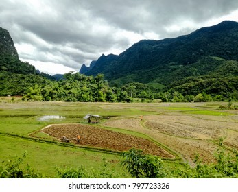 View over limestone mountains, paddy fields and farmers outside Ban Na village in the hinterlands of Muang Ngoy, Laos