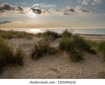 View over marram grass covered dunes towards the setting sun in northern France