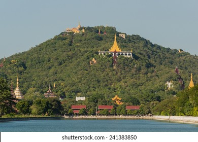 View over the moat of Mandalay Palace to Mandalay Hill with its many temples