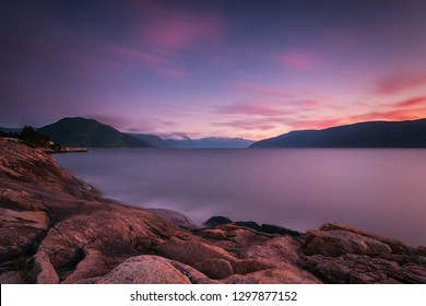 A view over a Norwegian fjord at sunset, taken with long exposure. Landscape at sunset