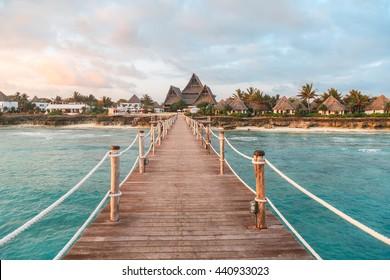 View over ocean coast with wooden bridge, bungalows, palms, pierce at sunrise, Nungwi, Kendwa, Zanzibar island, Tanzania