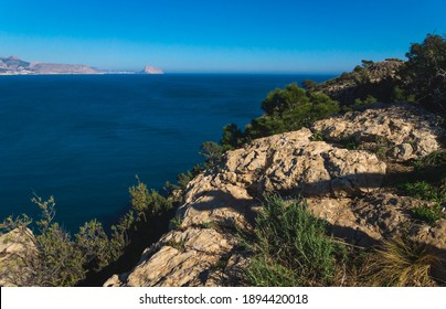 View over the ocean to the rock 'Ifach' of Calpe with steep overgrown cliffs from natural park 'Serra Gelada' in Albir, Costa Blanca, Spain