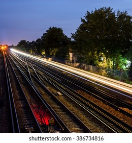 View over railway lines at mid-twilight with the light streak of a train that has recently passed. South London, UK.  Square version.