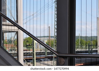 view over railway station with power supply lines from pedestrian bridge with glass front