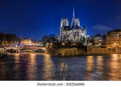 View over the river Seine onto illuminatred back side of Notre Dame de Paris Cathedral at night in, the world famous Gothic Roman Catholic cathedral in Paris, France