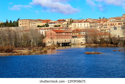 View over the river Tormes from an old water mill in the city of Salamanca, with other buildings behind.