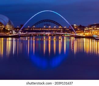 A view over the River Tyne, towards the Gateshead Millennium Bridge and Tyne Bridge in Newcastle upon Tyne, Northumberland, UK.