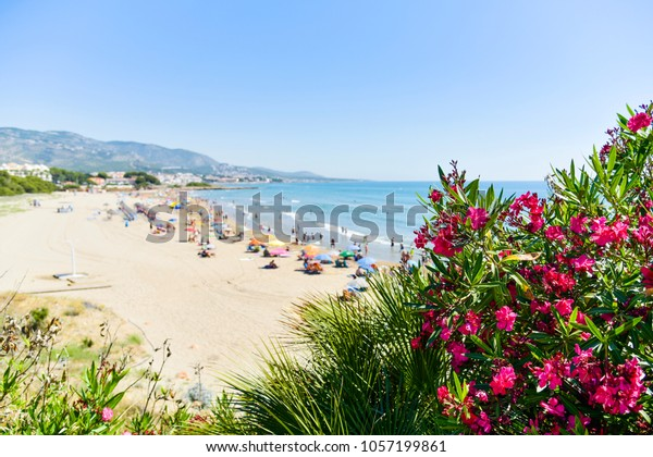 a view over the Romana beach in Alcossebre, in the Costa del Azahar, Spain, with unrecognizable people enjoying the warm weather