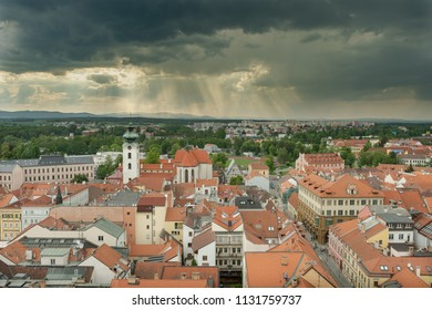 view over the roof tops of northern Budweis and the dominican monastery under a dark cloudy sky