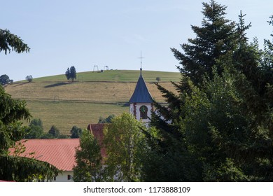 View over roofs past the church tower in Gernsbach to a ski lift in summer