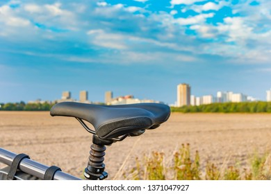 View over the saddle of a bicycle. In the background you can see a field and the unfocussed satellite town of Gropiusstadt in Berlin-Neukölln.