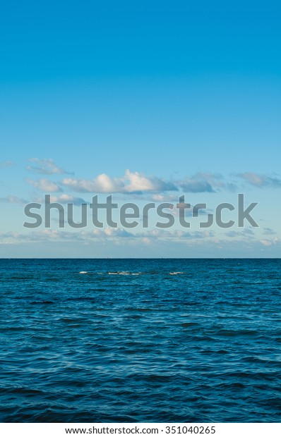 View over the sea; Wavy, dark blue sea with partly clouded sky