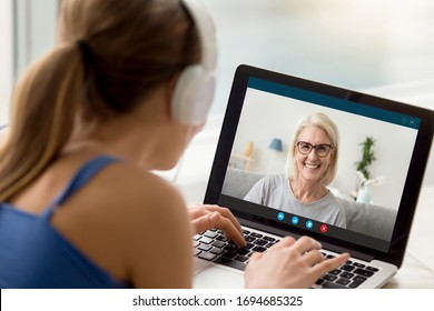 View over shoulder of adult daughter talks by video call with 50s mum. Pc screen view smiling elderly grandmother enjoy virtual chat videoconference with grown up granddaughter. New tech usage concept