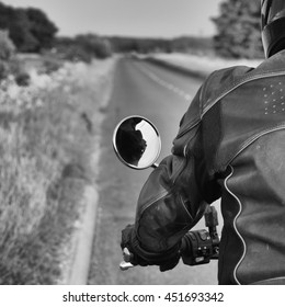 View over the shoulder of a motorbike rider showing open road.  Black and white.