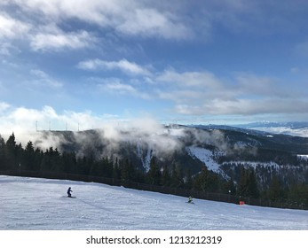 View over ski slopes with misty hills in the background