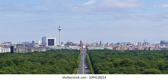 View over the skyline of Berlin with it's TV tower, the Brandenburg Gate and the Reichstag with many German flags from the Berlin Victory Column (Siegessäule).