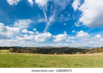View over the southern Eifel hills near Daun, Germany with blue sky.
