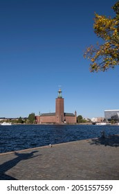 View over the Stockholm City Hall from terrace of troubadour Evert Taube on the island Riddarholmen with a shadow of the troubadour statue