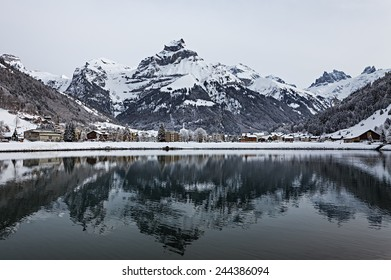 View over a Swiss Village by a lake in the Alps, covered in snow during winter. Engelberg, Switzerland.