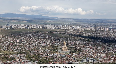 View over Tbilisi city and suburbs, Georgia with the St. Trinity Cathedral and Presidential Palace.