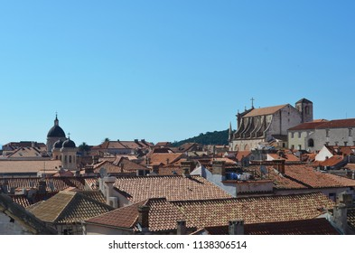 A view over the terracotta tiles covering the roofs of Dubrovnik. Some washing can be seen. The cathedral is to one side. The sky is blue.