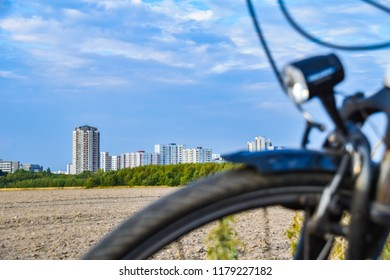 View over the unfocused front wheel of a bicycle across a field to the satellite town of Gropiusstadt in Berlin-Neukölln.