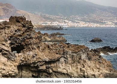 View over volcanic cliffs at the coastline of Los Cancajos in La Palma, Spain with Santa Cruz in the background.