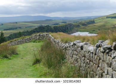 View over Hadrian's wall. Countryside landscape with trees, lake and dramatic sky with ancient stone wall as leading line