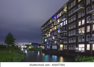 View over water to residential appartments with colorful illumination and lights at night near water in the  suburban Oosterheem, Zoetermeer, the Netherlands
